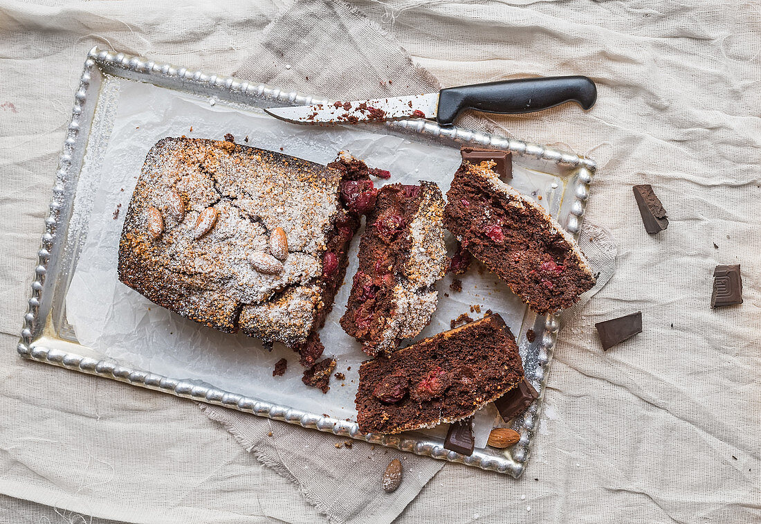 Cherry brownie with almond and dark chocolate cut into pieces on a silver tray over a piece of beige linen fabric