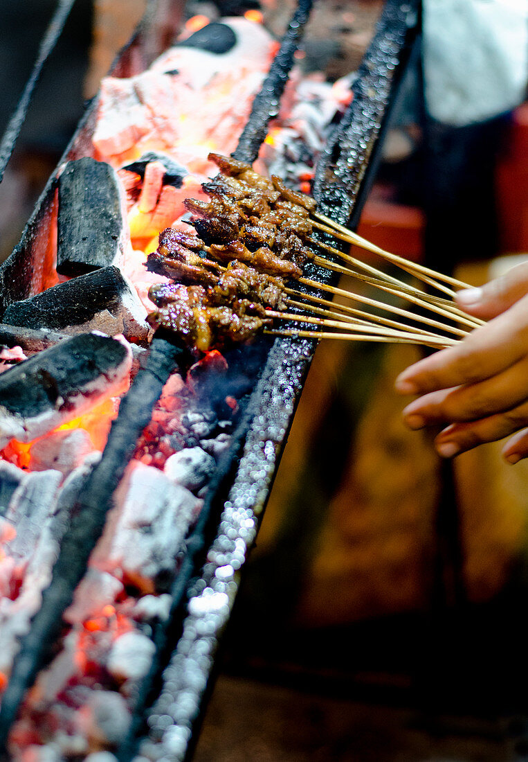 A close up of lamb satays on charcoal satay grill in Indonesia