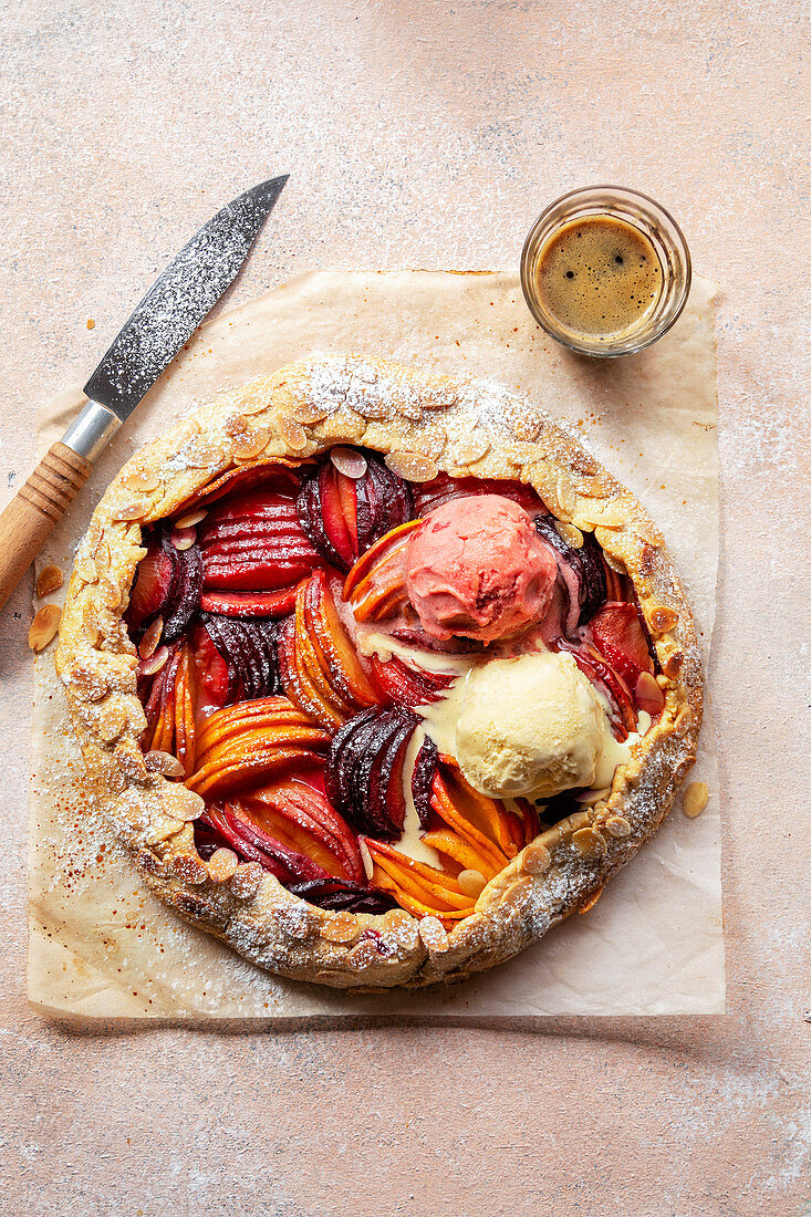 Freshly baked stone fruit galette with two dollops of ice cream on top