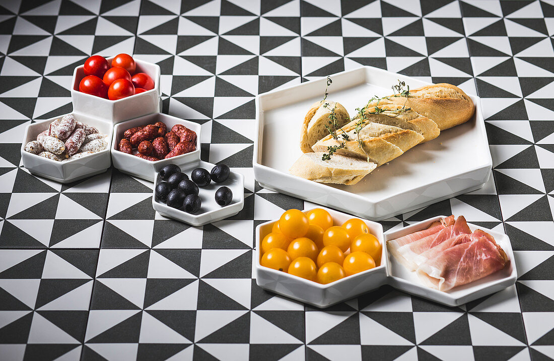 A white baguette with various antipasti on a patterned surface