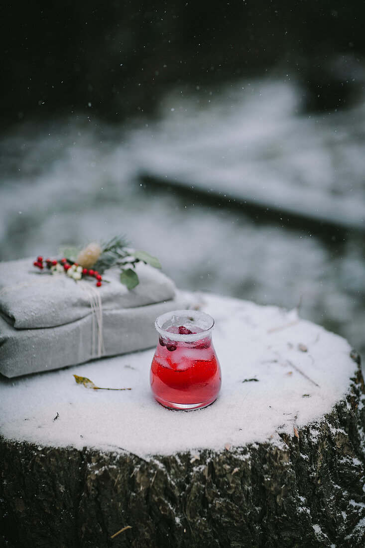 A cranberry drink with snow falling around it on a snow covered surface with a Christmas gift in the background