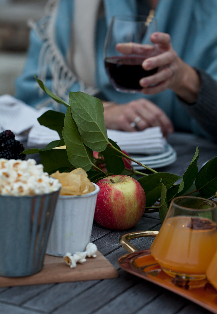 A Fall table with apples, popcorn, chips, apple cider with cinnamon and star anise, greenery and a woman holding a glass of red wine