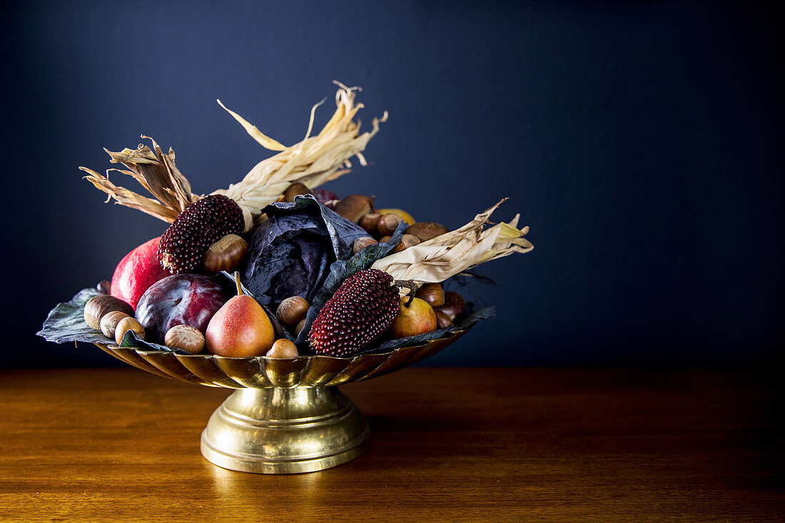 Autumnal fruit bowl with vegetables, corn on the cob and nuts