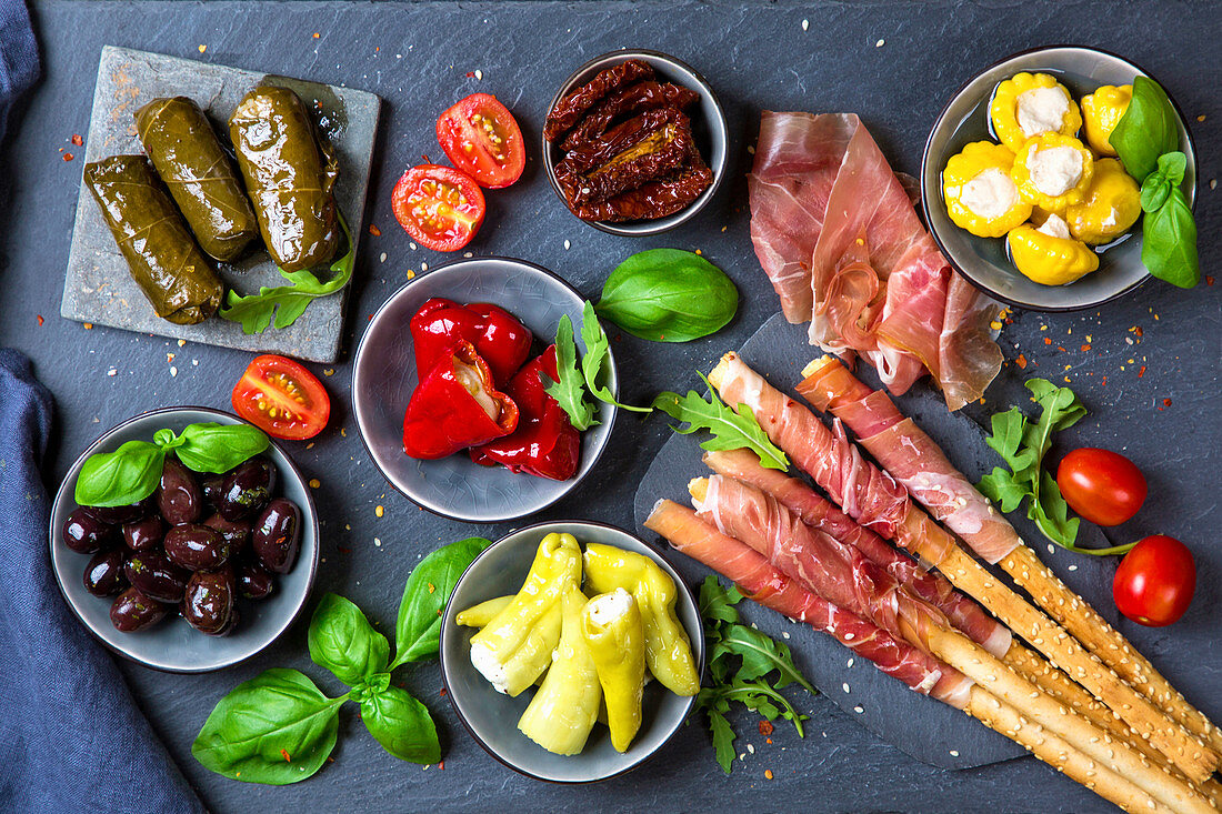Various Italian antipasti on a slate board