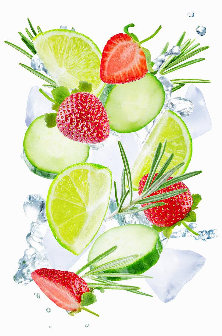 Fliegende Limetten, Gurkenscheiben, Rosmarin und Erdbeeren mit Eiswürfeln und Wassersplash
