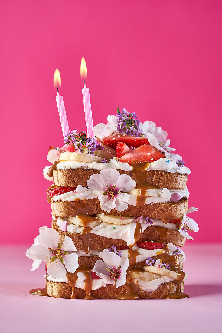A sandwich tower with bananas, caramel sauce, strawberries and flowers for a birthday party