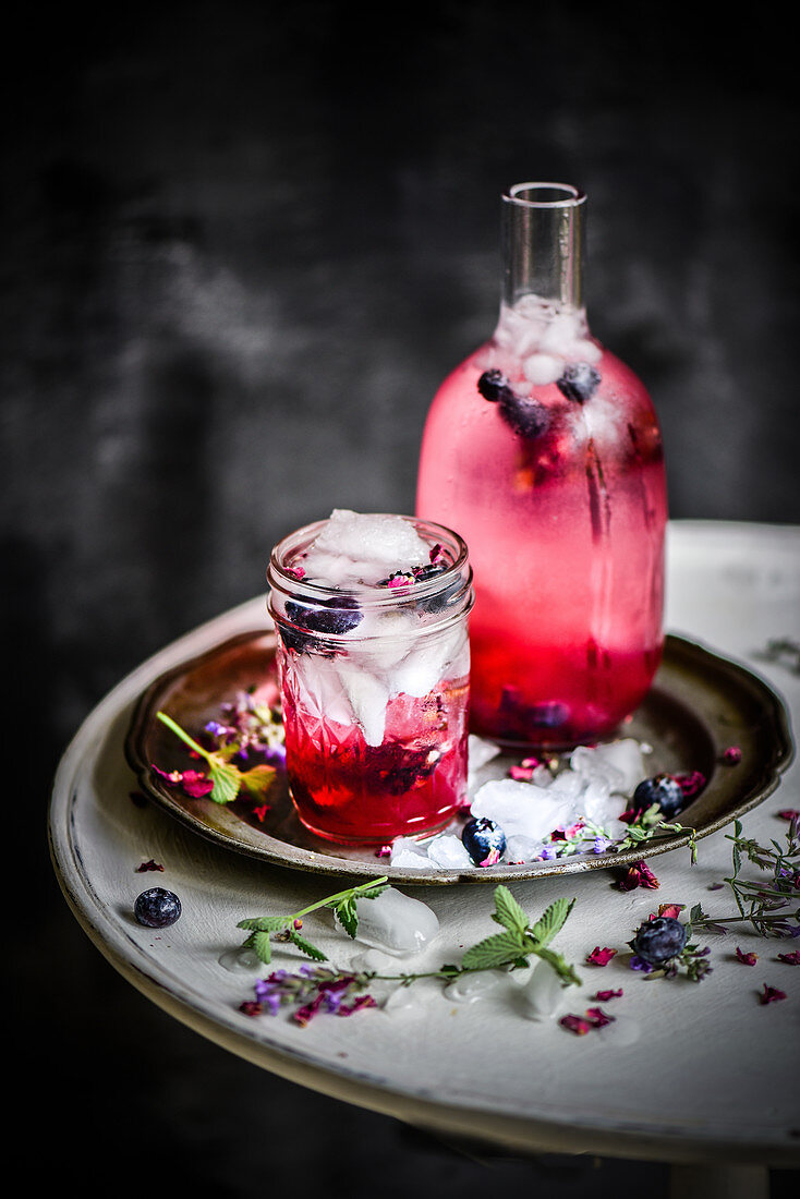 A glass and and jar of berry iced tea