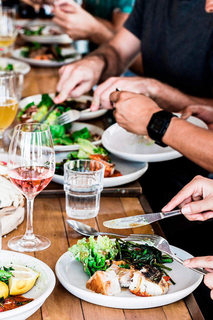 Laid table with summer salads and meat, hands while eating