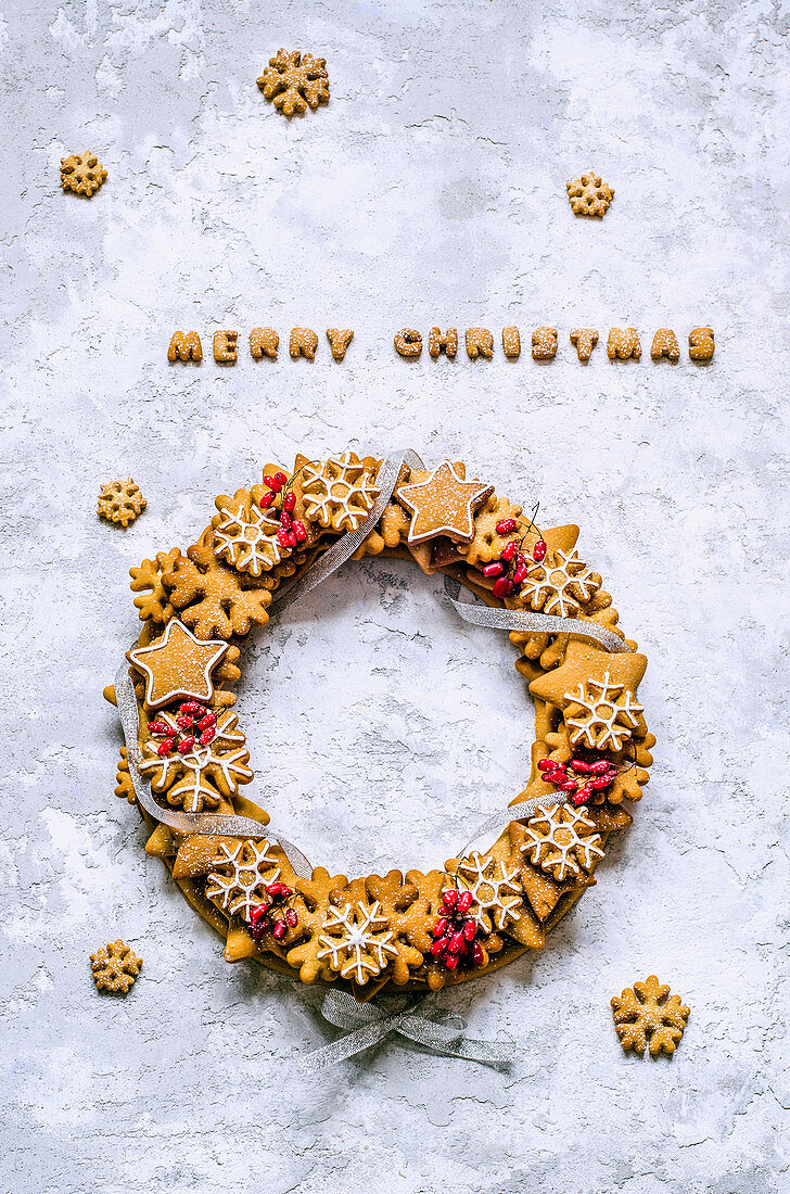 Christmas wreath of gingerbread dough in the shape of stars and snowflakes, barberry twigs, tied with a silver ribbon