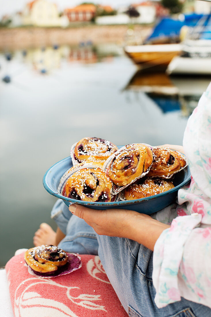 A woman holding a plate of blueberry buns with sugar nibs