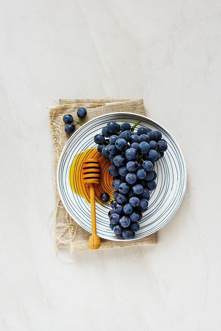 Fresh grape and honey on light background