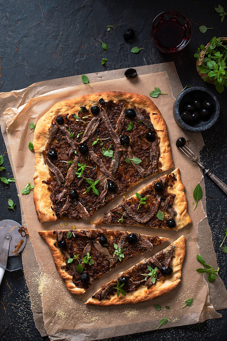Pissaladiere pizza with onions, anchovies and greek basil