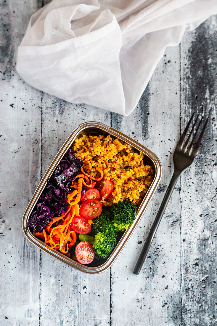 A bento box with quinoa, red cabbage, carrots, tomatoes and broccoli