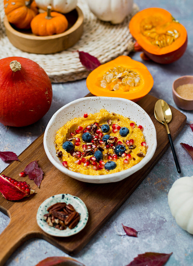 Millet and pumpkin porridge, served with pomegranate seeds and blueberries