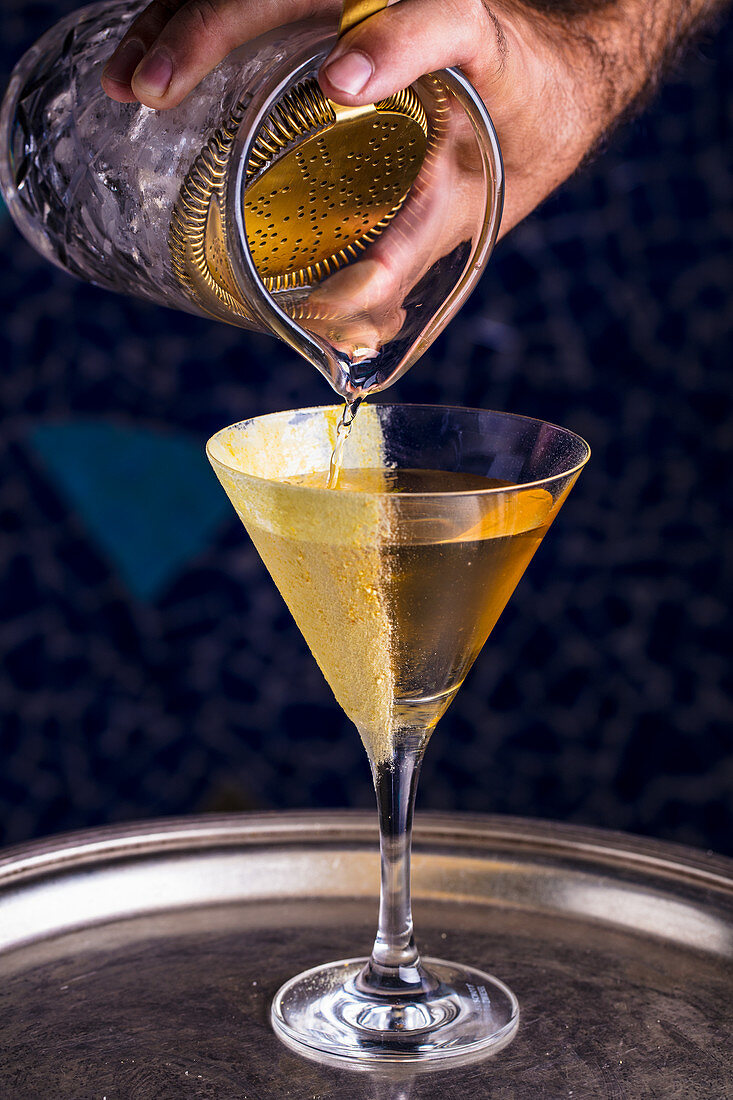 A martini being poured from a cocktail shaker into a glass