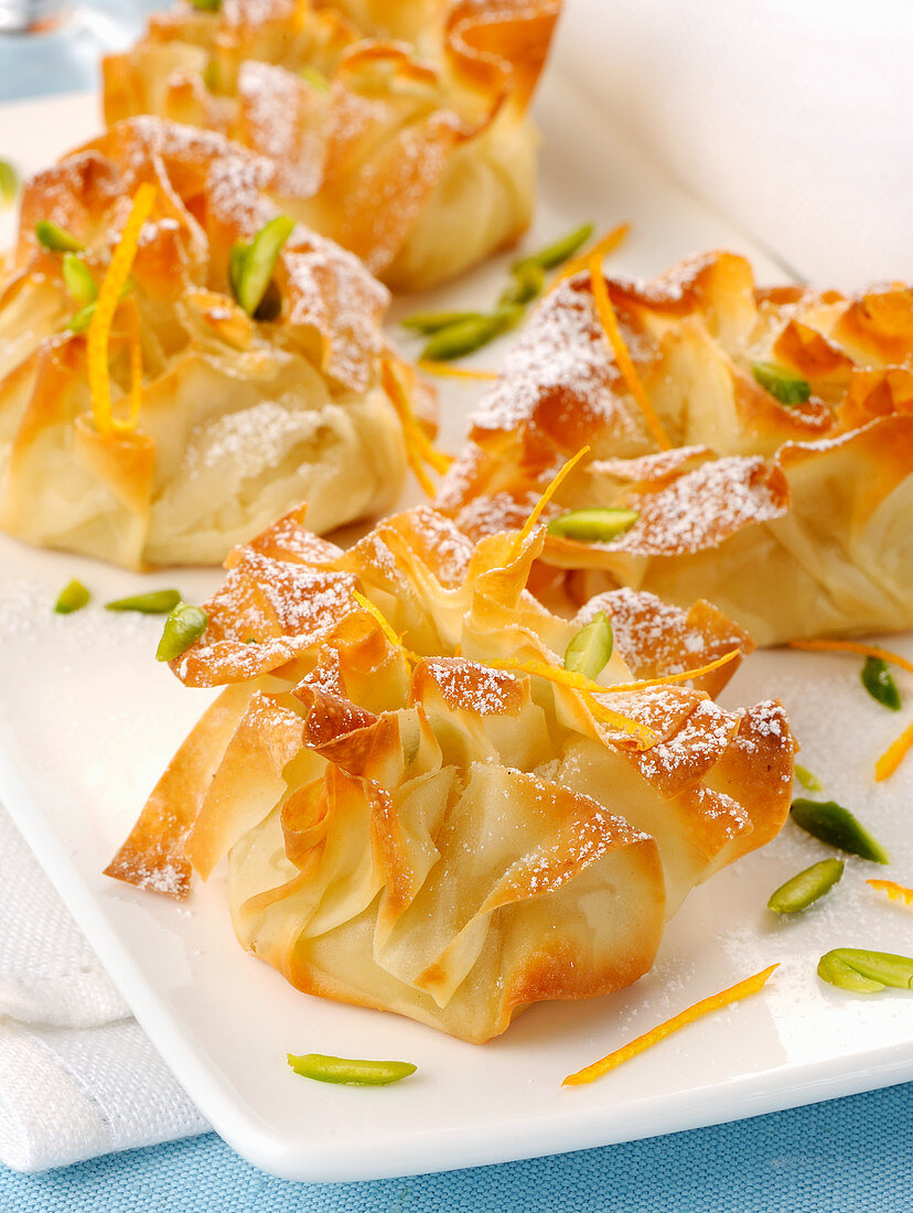 Stuffed filo pastry sacks with pistachios, orange zest and icing sugar
