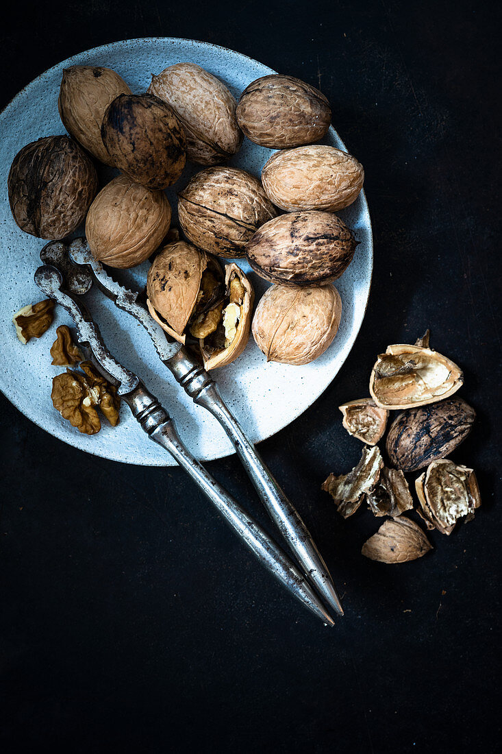 A plate of walnuts with a nut cracker