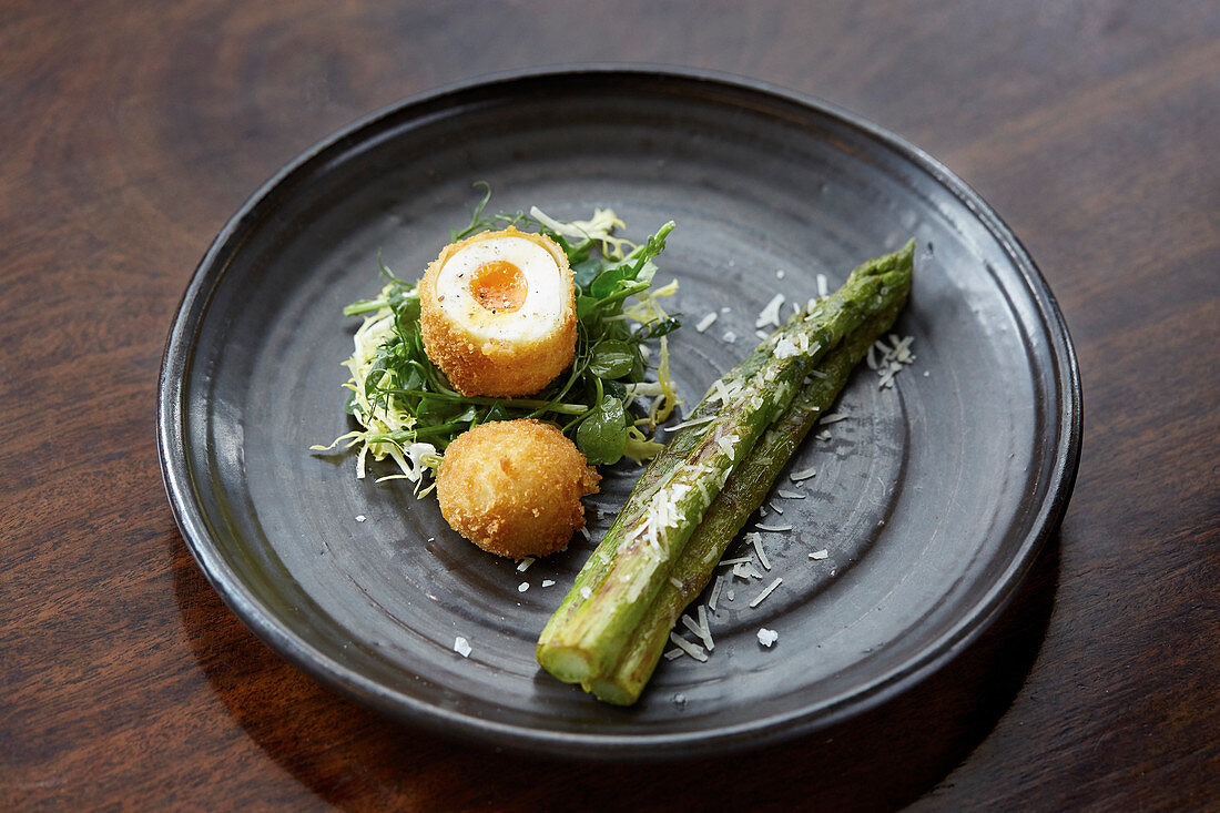 Deep fried boiled egg served with Asparagus and parmesan