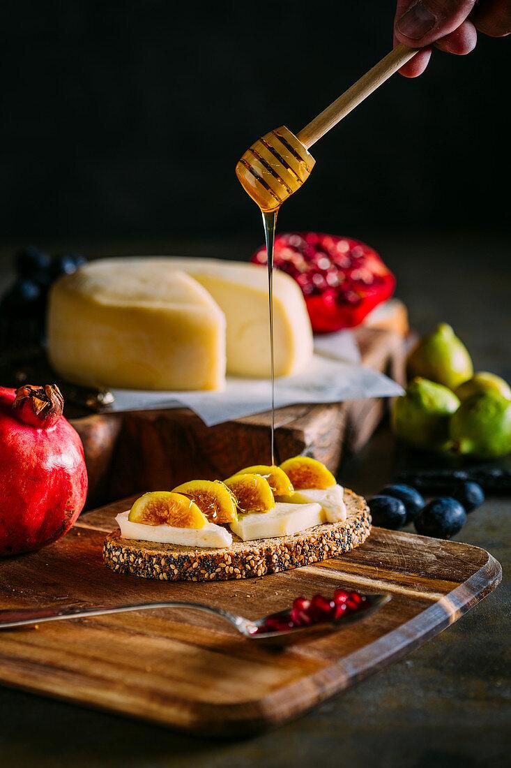 Ein Käse-Feigen-Brot mit Honig beträufeln