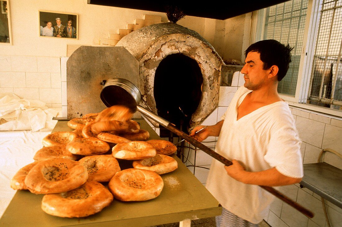 Israeli baker taking flat bread out of the oven