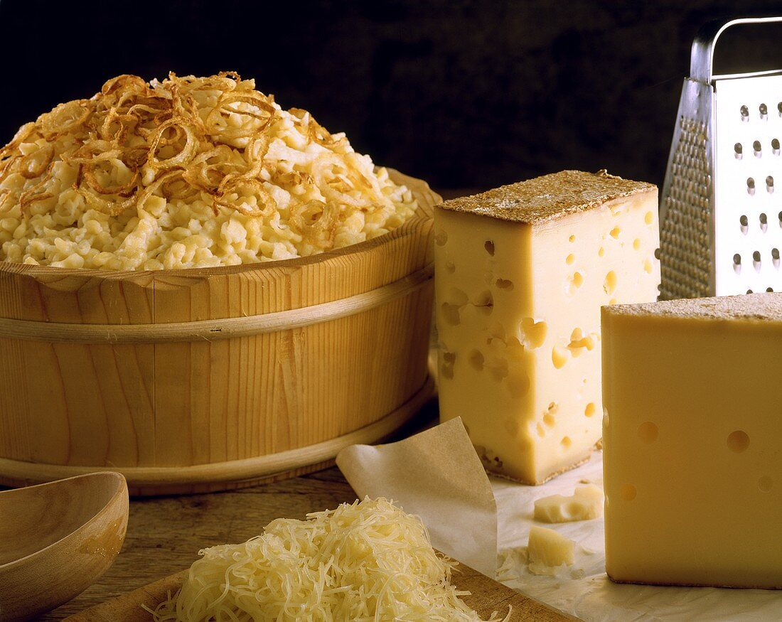 Cheese noodles (spaetzle) in bowl, cheese & grated cheese