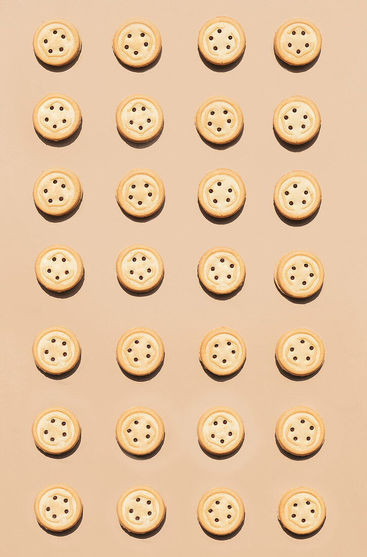 Round walnut cookies on a caramel coloured background