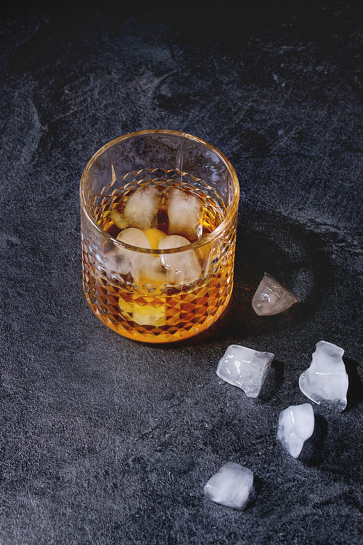 Glass of scotch whiskey on ice standing on black marble table