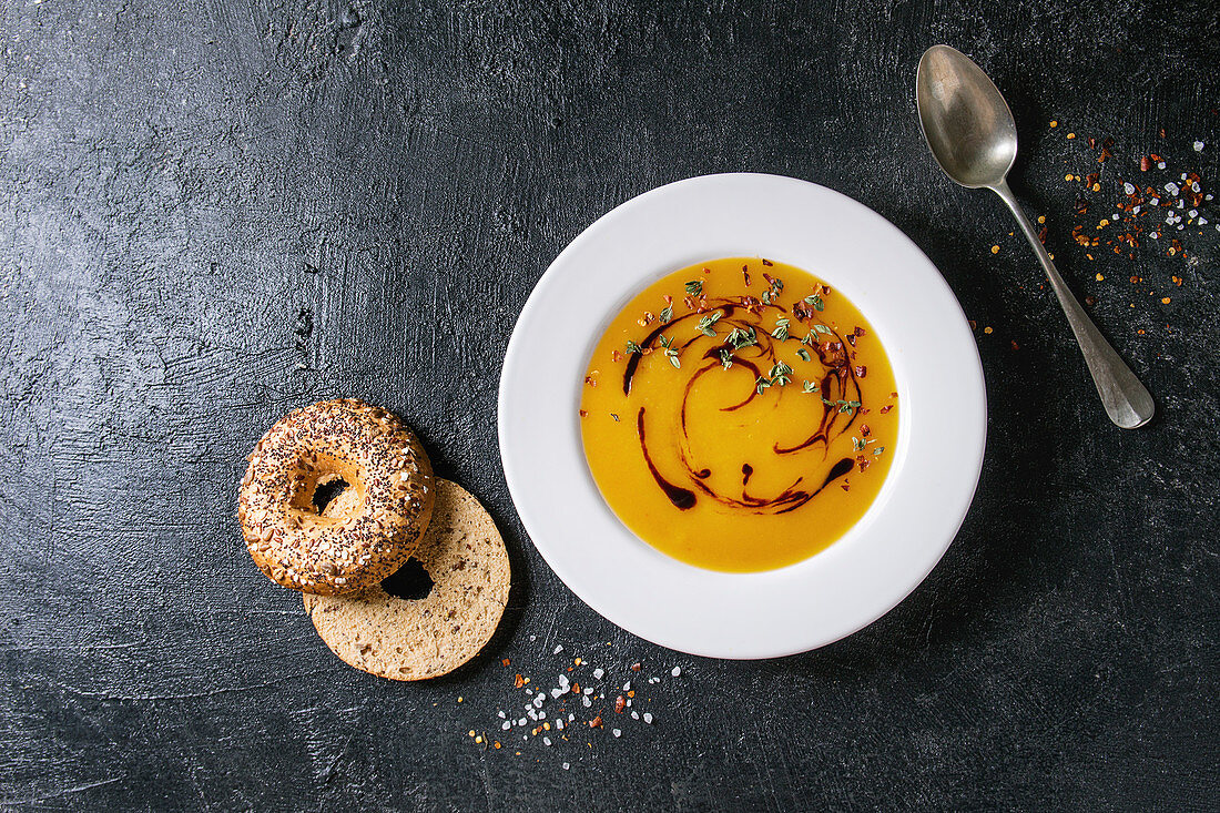 Plate of vegetarian pumpkin carrot soup decorated by balsamic vinegar and thyme