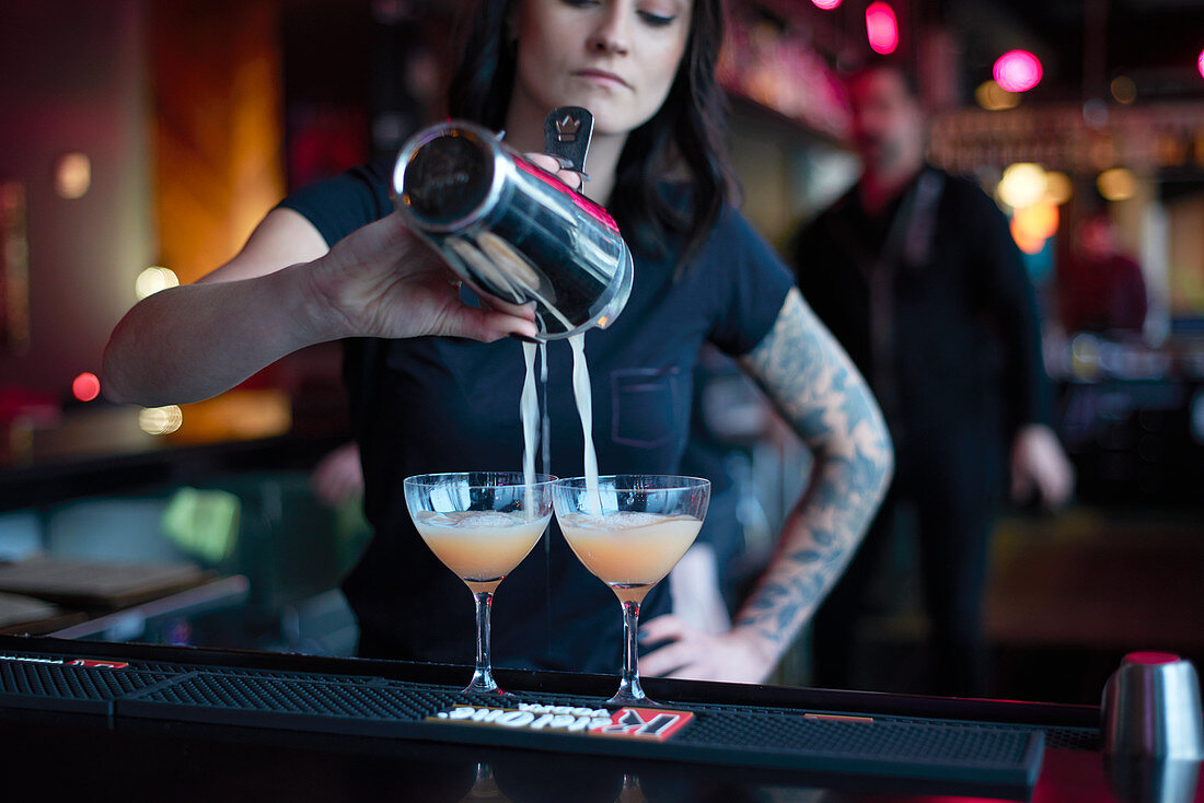 A bartender pouring cocktails into glasses