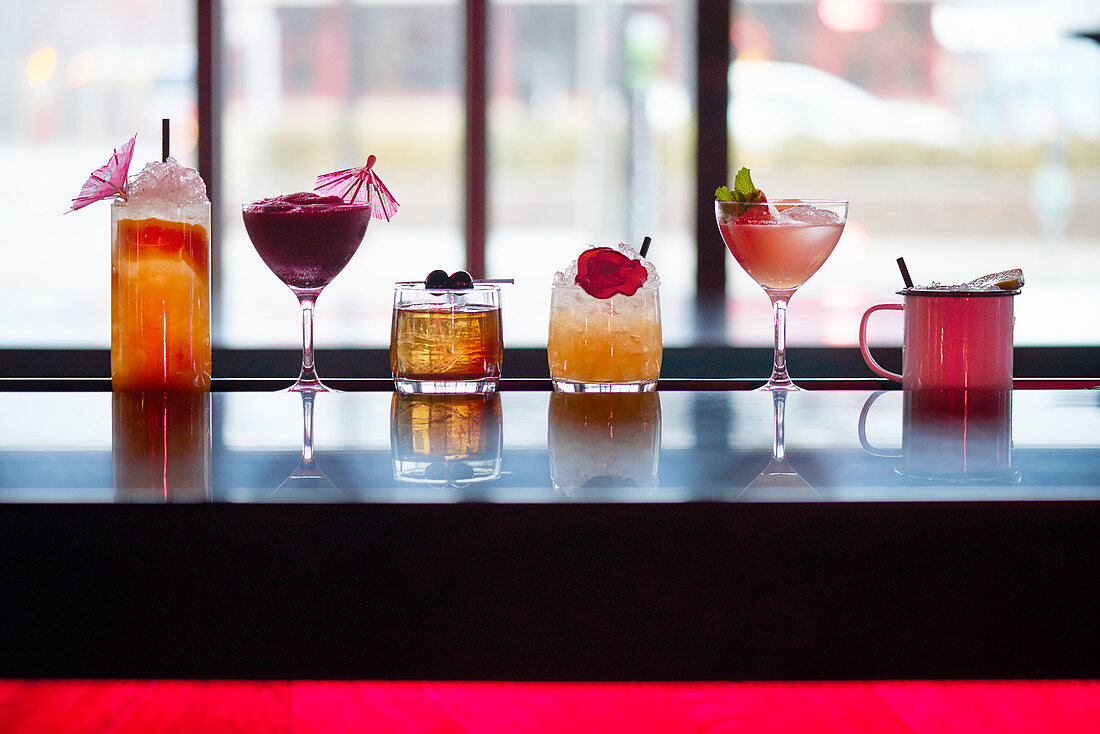 Six different cocktails and drinks on a bar counter