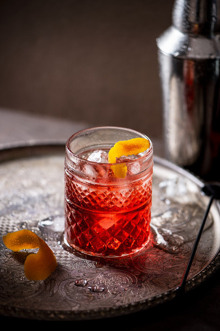 Negroni cocktail (vermouth, gin and campari) with orange zest