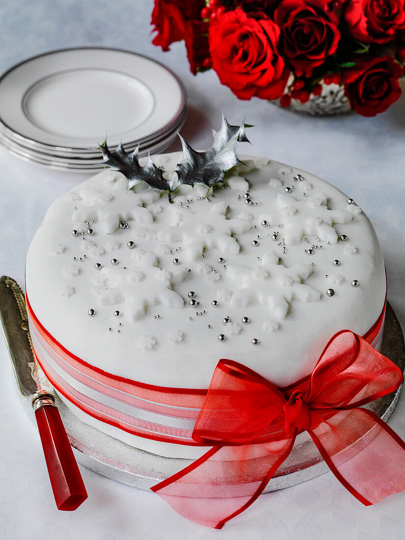 Christmas cake decorated with white fondant and red ribbon