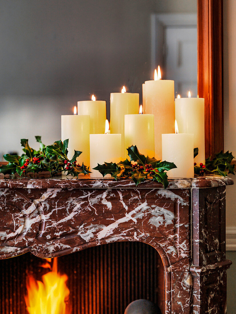 Christmas candles on mantelpiece with holly and open fire