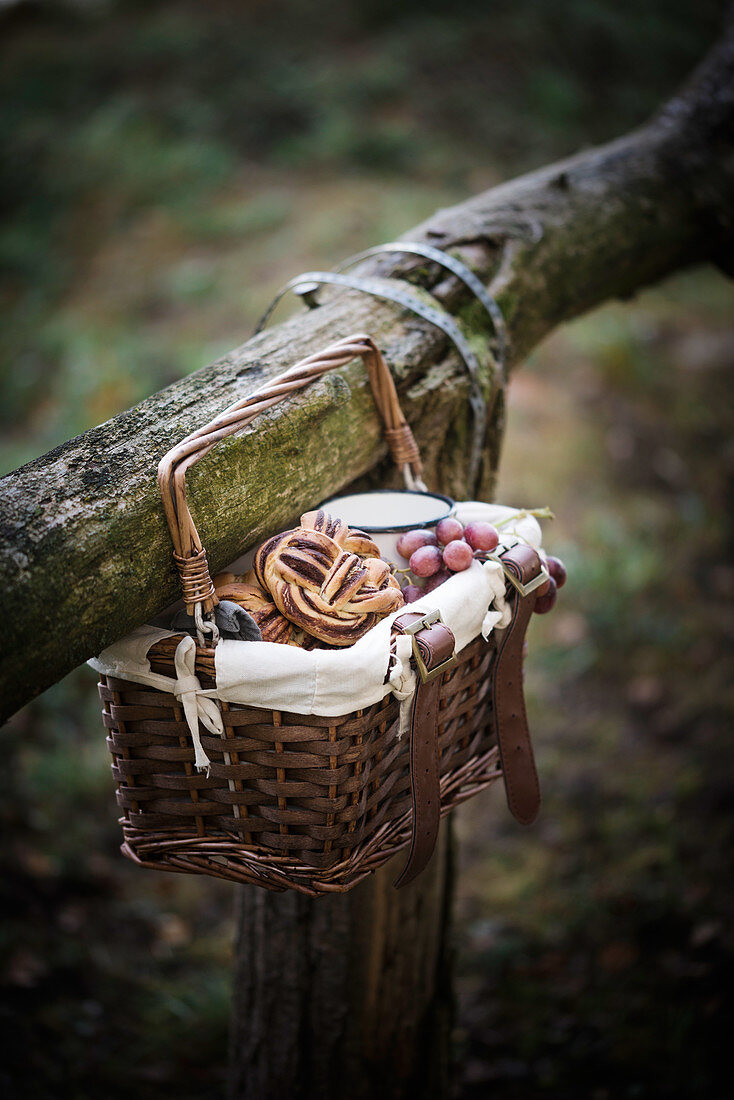 A picnic basket filled with a vegan chocolate bun, fruit and coffee hanging on a wooden railing