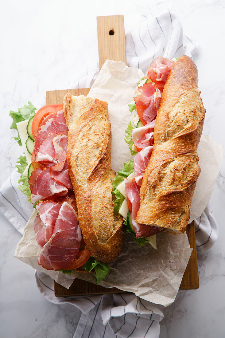 Fresh baguette sandwich bahn-mi styled, with ham, sliced cheese, tomatoes and fresh lettuce