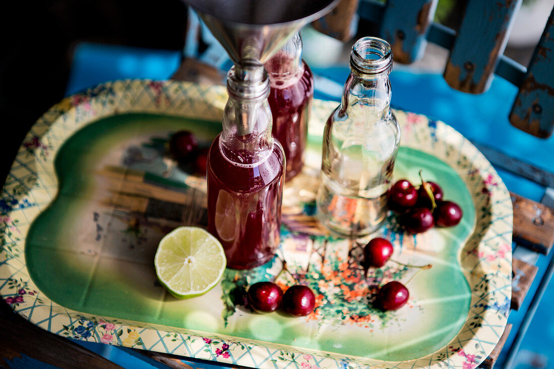 Cherry juice with limes and oranges being filled into bottles