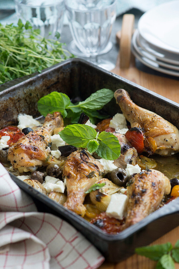 Oven-roasted chicken legs with olives, tomatoes and feta cheese