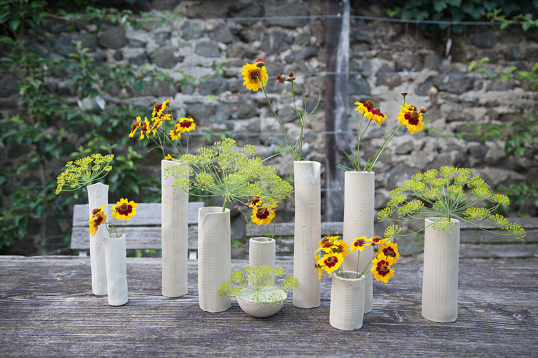 Calliopsis and fennel flowers in ceramic vases on garden table