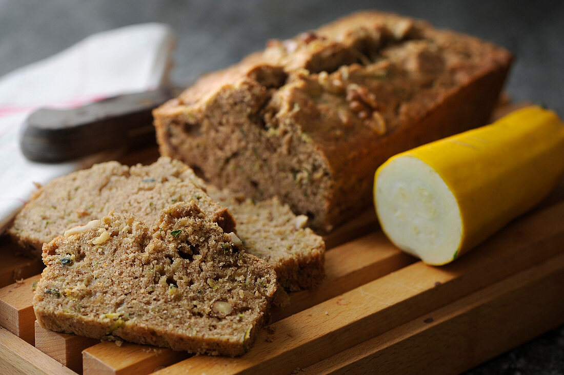 A courgette loaf cake with a yellow courgette, walnuts and cinnamon