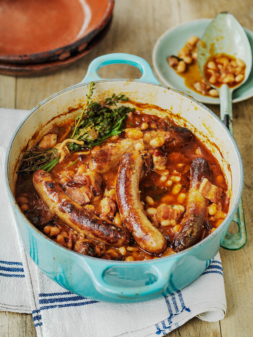 Slow cooked French cassoulet with sausages and beans in tomato sauce with bouquet garni