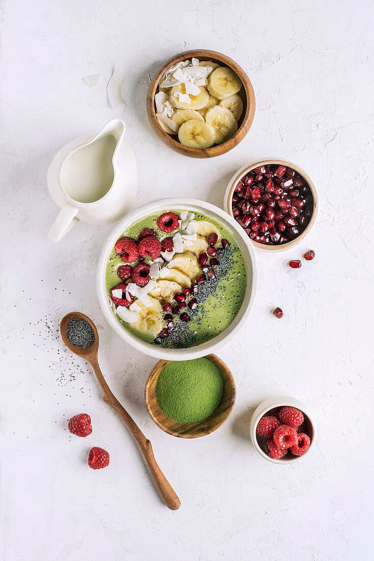 Bowl with healthy smoothie for breakfast in composition with various additives as fruit and matcha powder