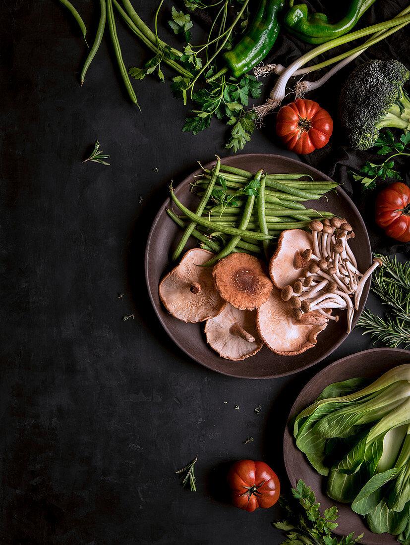 Frisches Gemüse, Pilze und Kräuter in Holzschalen und daneben