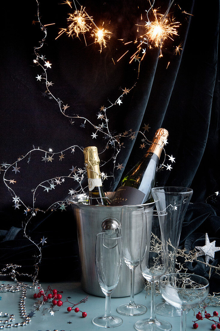 New Year's Eve party: champagne bottles in a chiller bucket decorated with a garland of stars and sparklers