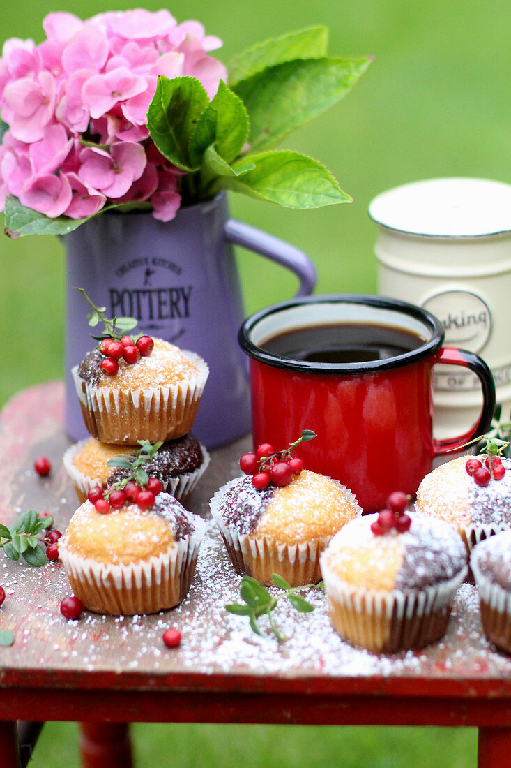 Two tone muffins garnished with redcurrants on a summer garden table