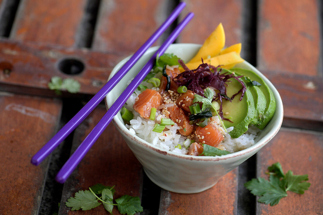 A poke bowl with raw marinated salmon, avocado and rice