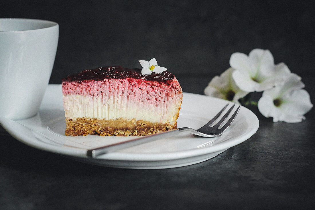 A slice of cheesecake with berries and a biscuit base