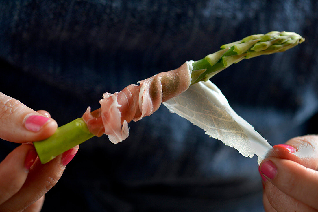 Parma ham being wrapped around a spear of green asparagus