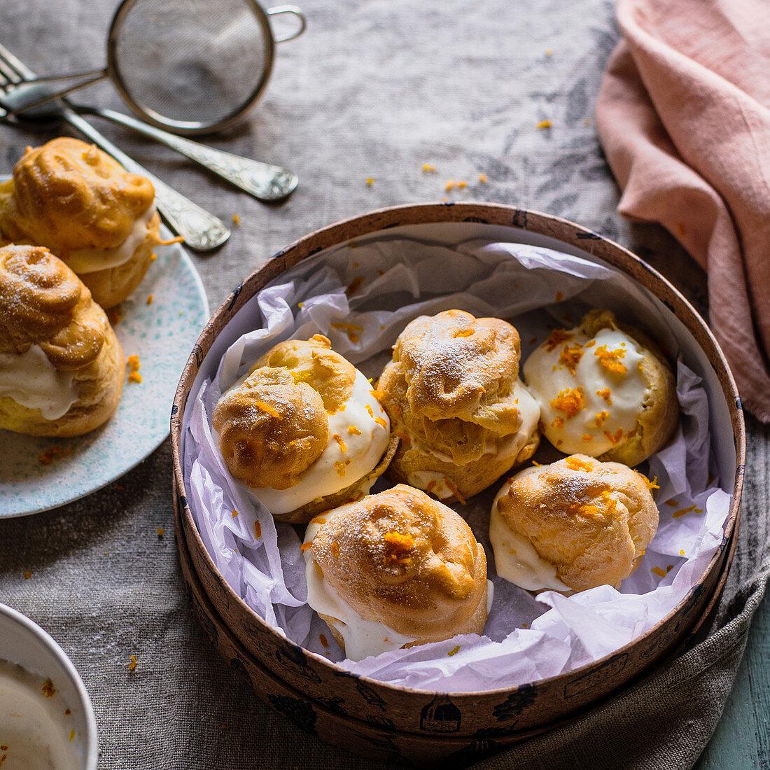 Cream puffs choux à la crème with orange custard and Italian meringue