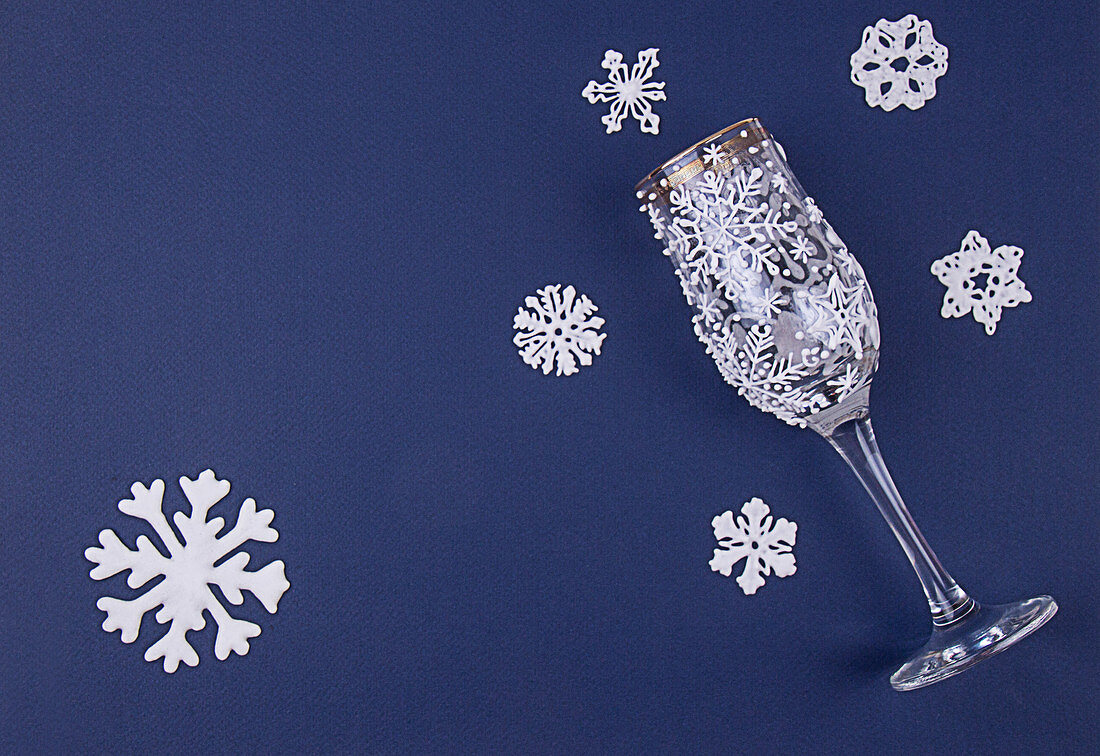 Decoration snoflakes made of sugar icing and wine glass decorated with icing on deep blue background