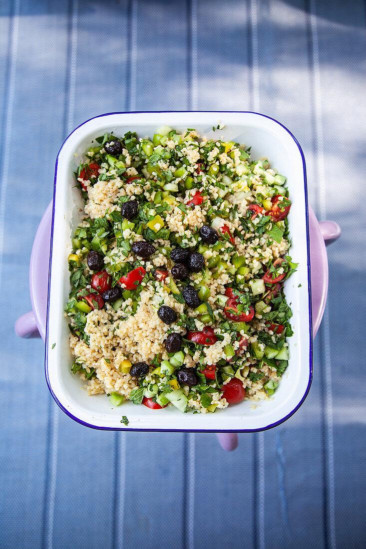 Bulgursalat mit getrockneten schwarzen Oliven und Kräutern